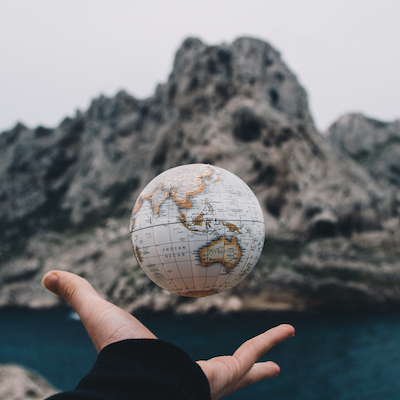 hand tossing globe in the air with rocks in background