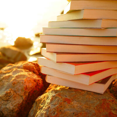 stack of books on rocky shore