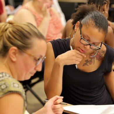 teachers looking down at worksheet